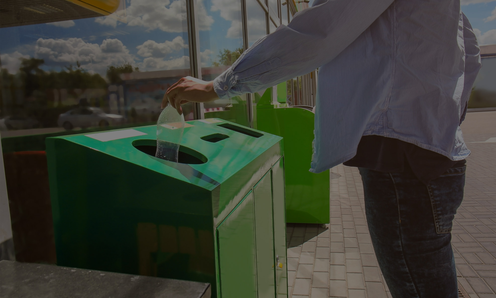 Person throwing away a plastic bottle in a recycling bin